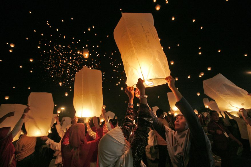 ** FILE ** Muslim women in Jakarta, Indonesia, take part in an attempt to break a world record for the most sky lanterns flown simultaneously in 2009. New Hampshire lawmakers have a bill this session to ban the use and sales of sky lanterns in the state. (AP Photo/Dita Alangkara)