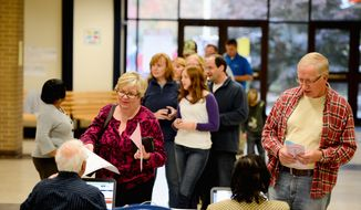 Voters wait in line to cast their ballots at the Hanover Precinct at Atlee High School, in Mechanicsville, Va., on Tuesday. Rob Wilhoite (below) makes his selections at the school. Turnout across the state was exceeding expectations, perhaps due in part to the hotly contested gubernatorial race. Voters wait in line to cast their ballots for Virginia Governor at the Hanover Precinct at Atlee High School, Mechanicsville, Va., Tuesday, November 5, 2013. (Andrew Harnik/The Washington Times) (photographs by andrew harnik/the washington times)