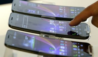 A visitor touches LG Electronics' G Flex smartphone, on display during a media event at the company's head offices in Seoul on Tuesday, Nov. 5, 2013. The G Flex, which features a curved display and battery, will go on sale Tuesday in the domestic market. (AP Photo/Lee Jin-man)