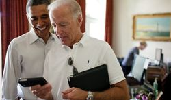 ** FILE ** Vice President Joe Biden and President Barack Obama look at an app on an iPhone in the Outer Oval Office, Saturday, July 16, 2011. (Official White House Photo by Pete Souza)