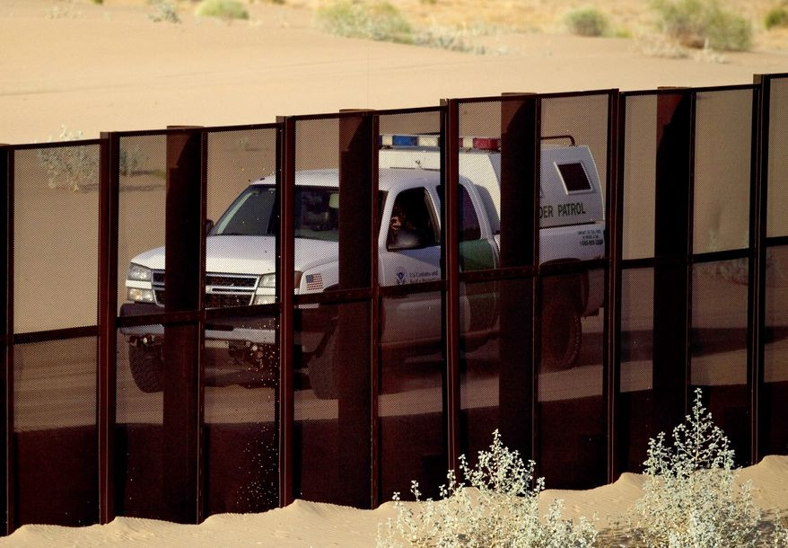 FILE - In this July 28, 2010, file photo, a U.S. border patrol vehicle drives along the U.S.-Mexico border fence near Yuma, Ariz., as seen from the outskirts of San Luis Rio Colorado, Mexico. The Border Patrol's parent agency decided to continue allowing agents to use deadly force against rock-throwers and assailants in vehicles, despite recommendations of a government commissioned review to end the practice.  (AP Photo/Guillermo Arias, File)