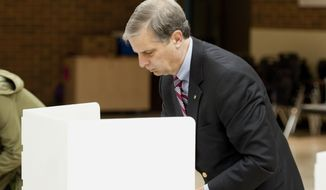 Harrisonburg Sen. Mark Obenshain, Republican candidate for attorney general,  marks his ballot at the Thomas Harrison Middle School West Central Precinct Tuesday, Nov. 5, 2013 in Harrisonburg, Va.  Obenshain faces Sen. Mark Herring, D-Loudoun.    (AP Photo/The Daily News-Record, Michael Reilly)