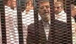 Ousted Egyptian President Mohammed Morsi speaks from the defendant's cage as he stands with co-defendants in a makeshift courtroom during a trial hearing in Cairo on Monday, Nov. 3, 2013. (AP Photo/Egyptian Interior Ministry)