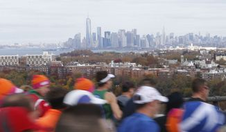 The Lower Manhattan skyline can be seen in the distance as runners cross the Verrazano-Narrows Bridge at the start of the New York City Marathon on Sunday, Nov. 3, 2013, in New York. (AP Photo/Jason DeCrow)