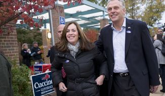 Virginia Democratic gubernatorial candidate Terry McAuliffe, right, and his wife, Dorothy McAuliffe, walk past a sign for his Republican opponent, Ken Cuccinelli, after voting on election day Tuesday, Nov. 5, 2013, in McLean, Va. (AP Photo/Jacquelyn Martin)
