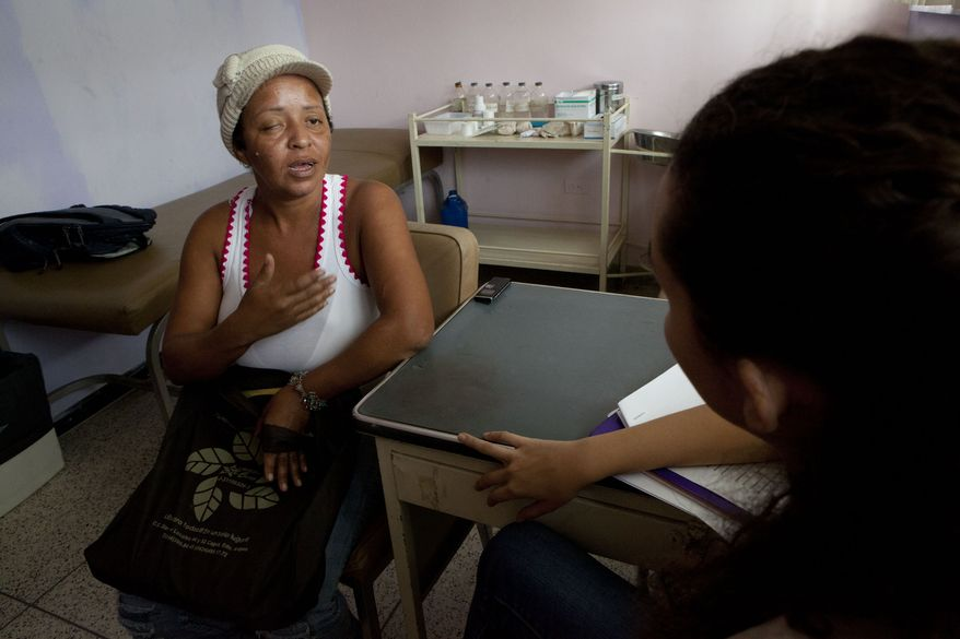 Evelina Gonzalez speaks with a psychologist at the Central Hospital in Maracay, Venezuela, on Oct. 28, 2013. She was supposed to have surgery in July following chemotherapy but was forced to shuttle from hospital to hospital in search of an available operating table, her tumor in the meanwhile more than doubling in size. The hospital's physicians sent some 300 patients in need of cancer operations home last month. Supply shortages, unsanitary conditions and equipment failures have forced them to scratch all but emergency surgeries. (AP Photo/Ariana Cubillos)