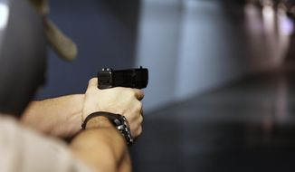 A man fires a handgun at Sandy Springs Gun Club and Range in Sandy Springs, Ga., on Jan. 4, 2013. (Associated Press) ** FILE **