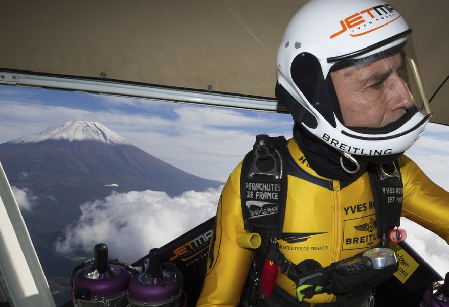 In this photo taken Friday, Oct. 30, 2013 and provided by Breitling, Yves Rossy, known as the Jetman, gets ready to jump from a helicopter near Mount Fuji in Japan. The Swiss aviator jumped from a helicopter at an altitude of 3,600 meters (11,811 feet) and successfully flew the jet-powered carbon-Kevlar Jetwing around the 3,776-meter (12,388-foot)-tall mountain, Japan's highest peak, which was recognized as a UNESCO World Heritage site in June. (AP Photo/Andre Bernet, Breitling) EDITORIAL USE ONLY, NO SALES