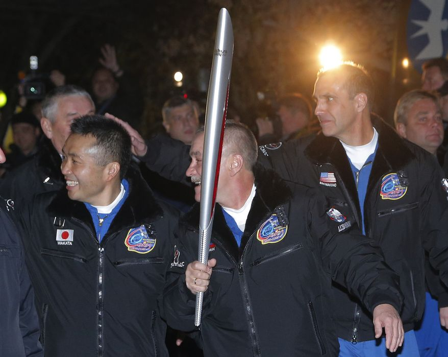 From  left, Japanese astronaut Koichi Wakata, Russian cosmonaut Mikhail Tyurin and U.S. astronaut Rick Mastracchio, crew members of the mission to the International Space Station (ISS), walk to a bus from a hotel with an Olympic torch prior the launch of a Soyuz-FG rocket at the Russian leased Baikonur cosmodrome, Kazakhstan, Thursday, Nov. 7, 2013. The crew will deliver Olympic torch to space as part of the ongoing Olympic torch relay. The torch will be brought back along with the station's current crew. (AP Photo/Dmitry Lovetsky)