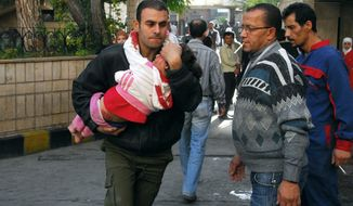 A Syrian man carries a girl who was wounded when a bomb blast hit the entrance to the main train station in Damascus, Syria, on Wednesday, Nov. 6, 2013. Bombs targeting the entrance of a landmark Ottoman railway building and a feared security agency in Syria's southeast killed more than a dozen people on Wednesday, activists reported. (AP Photo/SANA)