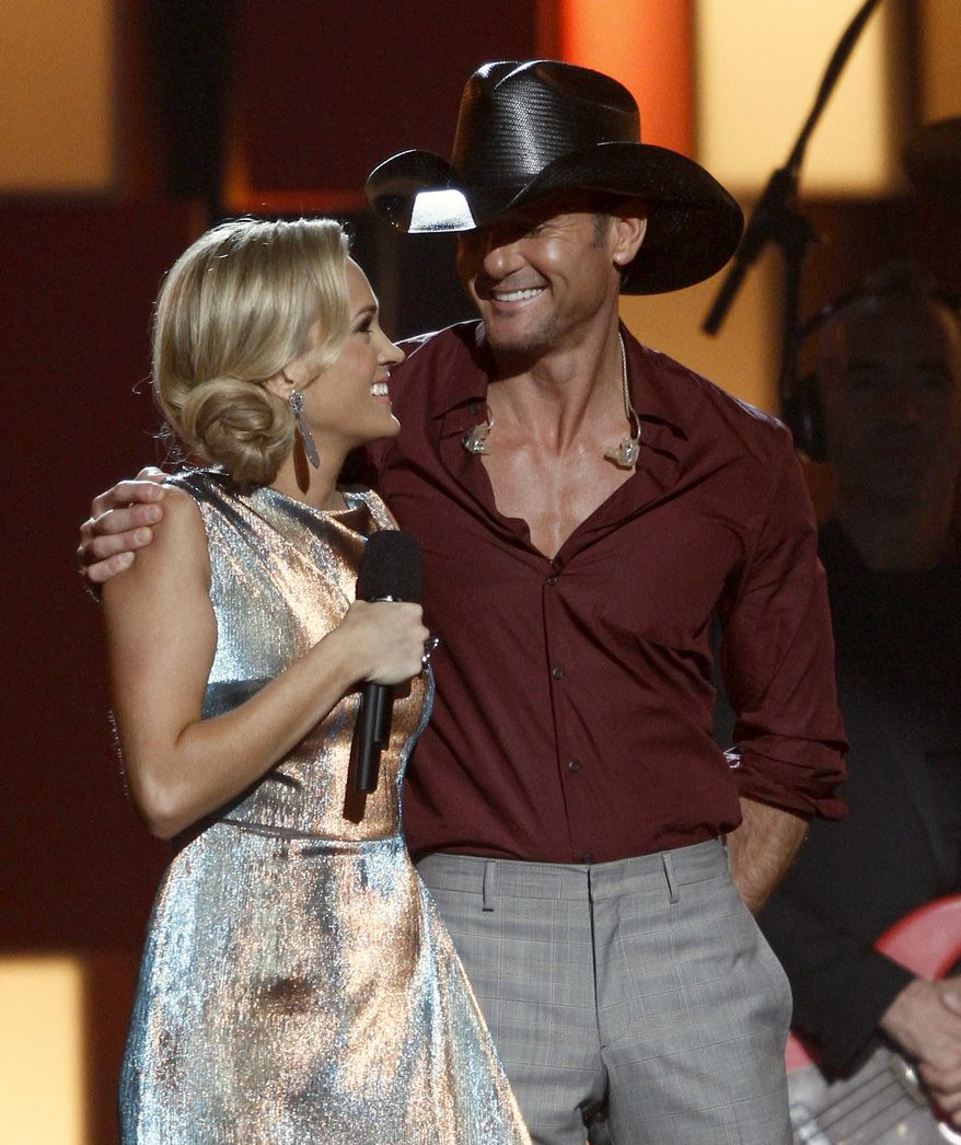 Carrie Underwood, left, and Tim McGraw appear onstage at the 47th annual CMA Awards at Bridgestone Arena on Wednesday, Nov. 6, 2013, in Nashville, Tenn. (Photo by Wade Payne/Invision/AP)