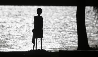 ** FILE ** A sculpture of a woman and a child is silhouetted against the water of Schwedsee lake at Nazi death camp Ravensbrueck about 100 kilometers (62 miles) north of Berlin, Thursday, Nov. 7, 2013.  (AP Photo/Markus Schreiber)
