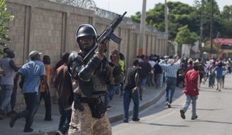 A police officer holds up his weapon as anti-government protesters are dispersed after a peaceful march turned violent, in Port-au-Prince, Haiti, Thursday, Nov. 7, 2013. An anti-government protest in Haiti turned violent Thursday with police firing tear gas and counter-demonstrators throwing stones at the marchers. Sporadic demonstrations have taken place in Haiti's capital in recent weeks calling for the resignation of President Michel Martelly. Protesters say his government isn't doing enough to improve living conditions and they want him to hold overdue legislative and local elections. (AP Photo/Dieu Nalio Chery)