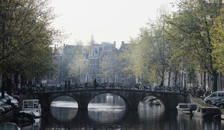 Pedestrians and bicyclists cross a bridge over a canal in the center of Amsterdam on Friday, Nov. 8, 2013. (AP Photos/Margriet Faber)