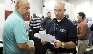 Brian McDonald (right), a recruiter with Wise Metals Group, takes a look at International Paper employee Jay Moody's resume during a job fair at the Courtland Baptist Church in Courtland, Ala., on Thursday, Nov. 7, 2013. (AP Photo/Jeronimo Nisa, Decatur Daily)