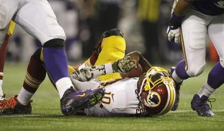 Washington Redskins quarterback Robert Griffin III lies on the field after getting sacked during the second half of an NFL football game against the Minnesota Vikings, Thursday, Nov. 7, 2013, in Minneapolis. The Vikings won 34-27. (AP Photo/Jim Mone)