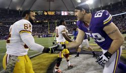 Washington Redskins tight end Niles Paul, left, and Minnesota Vikings defensive end Jared Allen shake hands before the coin toss in an NFL football game, Thursday, Nov. 7, 2013 in Minneapolis. (AP Photo/Jim Mone)