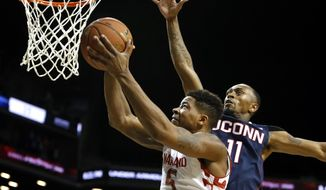 Maryland's Nick Faust (5) goes to the basket against Connecticut's Ryan Boatright (11) during the second half of an NCAA college basketball game Friday, Nov. 8, 2013, in New York. UConn defeated Maryland 78-77. (AP Photo/Jason DeCrow)