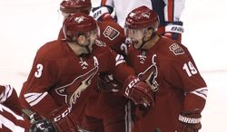 Phoenix Coyotes captain Shane Doan (19) celebrates with teammates Keith Yandle (3) and Oliver Ekman-Larsson (23) after his power-play goal against the Washington Capitals during the first period of an NHL hockey game, Saturday, Nov. 9, 2013 in Glendale, Ariz. (AP Photo/Ralph Freso)