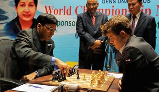 ** FILE ** Defending champion India's Viswanathan Anand, left, makes a move against Norway's Magnus Carlsen during the first game of the World Chess Championship in Chennai, India, Saturday, Nov. 9, 2013. The game ended in a draw. (AP Photo)
