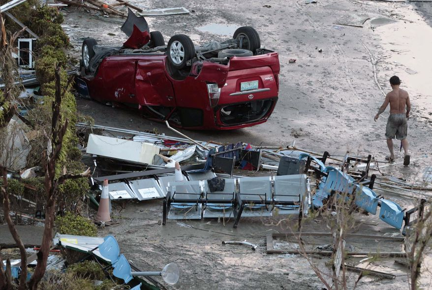 A resident passes by toppled car outside an airport terminal after powerful Typhoon Haiyan slammed into Tacloban city, Leyte province central Philippines on Saturday, Nov. 9, 2013. Rescuers in the central Philippines counted at least 100 people dead and many more injured Saturday, a day after one of the most powerful typhoons on record ripped through the region. AP Photo/Aaron Favila)