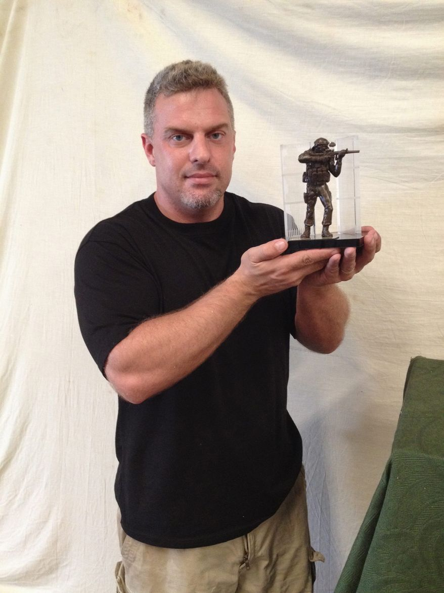 Gregory Marra shows a desktop version of a statue honoring SEAL Team 6's Operation Neptune Spear.