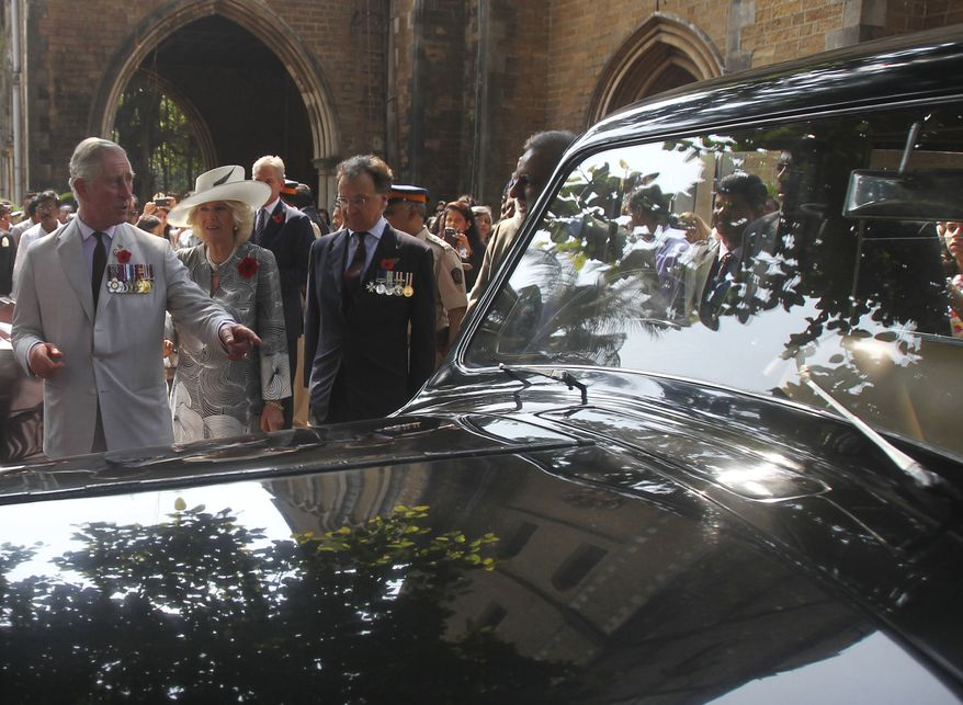 Britain's Prince Charles (left), along with wife Camilla, the Duchess of Cornwall, looks at a vintage car as he leaves after a Remembrance Day service at the Afghan Church in Mumbai on Sunday, Nov. 10, 2013. Charles and Camilla are on a nine-day visit to India.( AP Photo/Rafiq Maqbool, Pool)