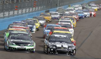 Pole winner Jimmie Johnson (48), right, and Denny Hamlin (11) lead the field into turn one during the first lap of the AdvoCare 500 NASCAR Sprint Cup Series auto race at Phoenix International Raceway, Sunday, Nov. 10, 2013 in Avondale, Ariz. (AP Photo/Ralph Freso)