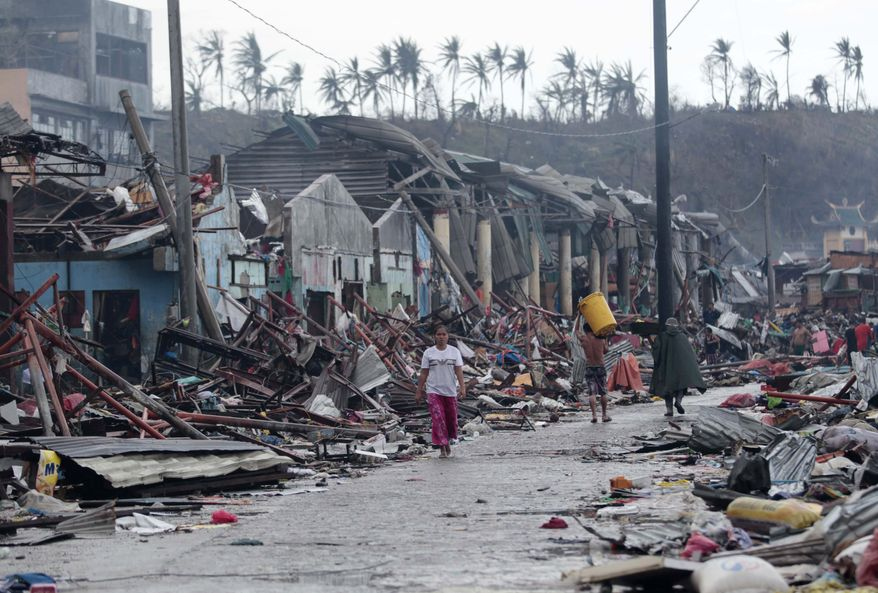 On Sunday, Nov. 10, 2013, residents of Tacloban city, on the central Philippines island of Leyte, walk past structures damaged by Typhoon Haiyan on Friday. (AP Photo/Aaron Favila)