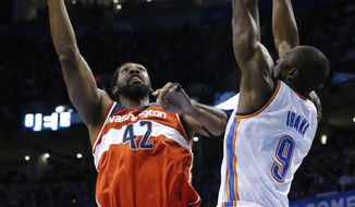 Washington Wizards forward Nene (42) shoots in front of Oklahoma City Thunder forward Serge Ibaka (9) in the first quarter of an NBA basketball game in Oklahoma City, Sunday, Nov. 10, 2013. (AP Photo/Sue Ogrocki)