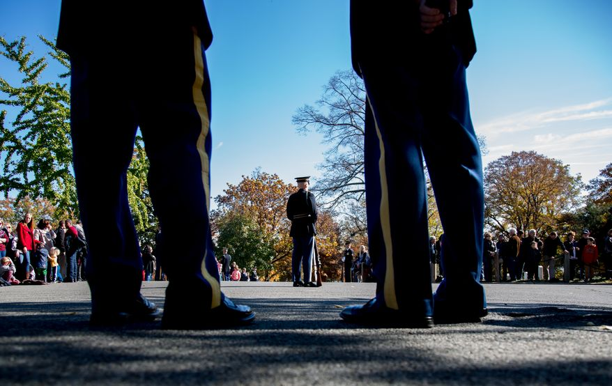 Service members attached to the Army's Honor Guard stand watch over the road leading up to the Tomb of the Unknown Solider during a Veteran's Day ceremony, in Arlington, VA., Monday, November 11, 2013.(Andrew S. Geraci/The Washington Times)