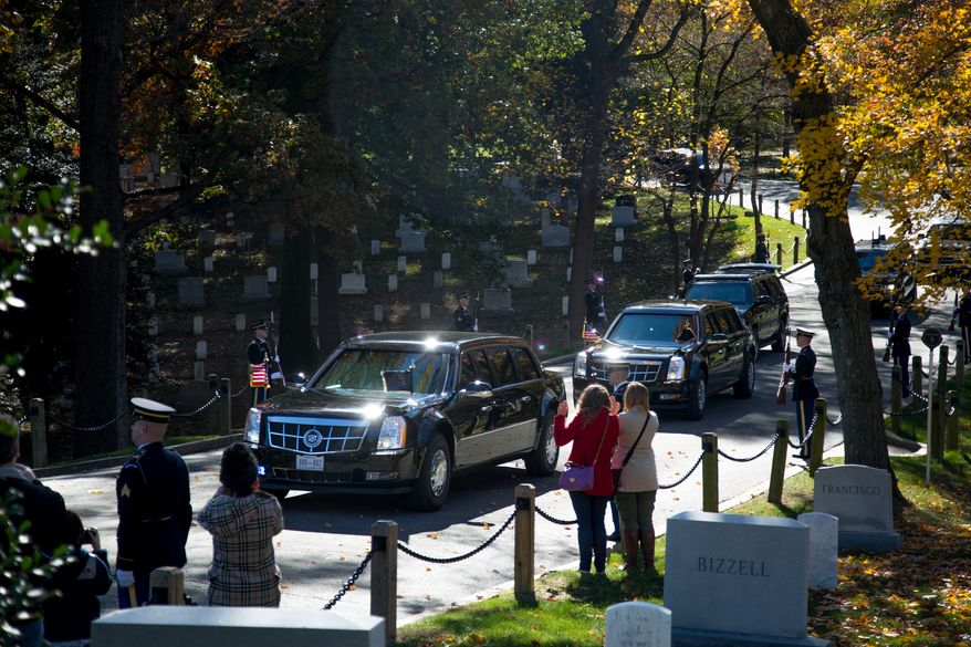 Visitors to the Arlington National Cemetery wave as the President's vehicle drives down the road leading up to the Tomb of the Unknown Solider during a Veteran's Day ceremony, in Arlington, VA., Monday, November 11, 2013.(Andrew S. Geraci/The Washington Times)