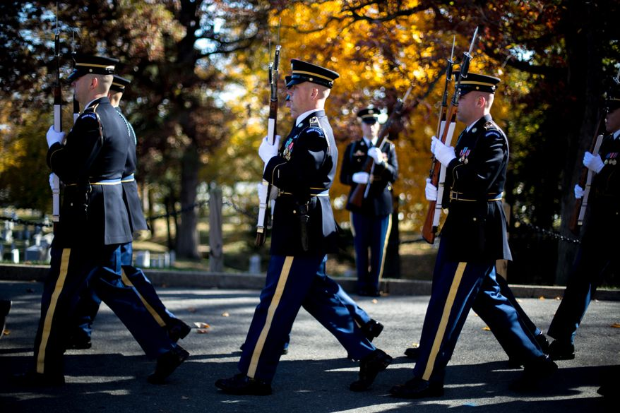 US Army service members attached to the Honor Guard, march down the road leading to the Tomb of the Unknown Soldier at Arlington National Cemetery during a Veteran's Day ceremony, in Arlington, VA., Monday, November 11, 2013.(Andrew S. Geraci/The Washington Times)