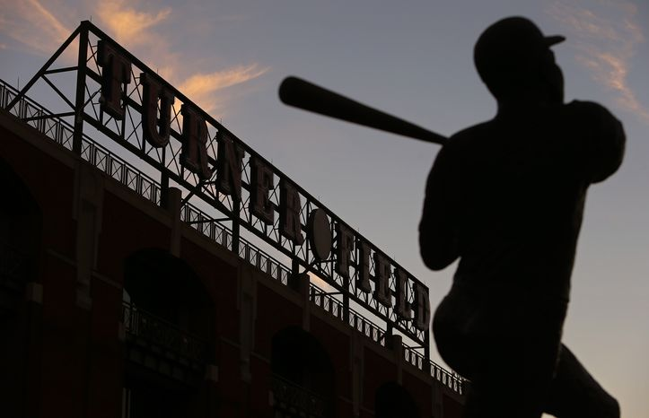 The sun sets over Turner Field and a statue of Hank Aaron on Monday, Nov. 11, 2013, the day the Braves announced that they would be moving to Cobb County.  (AP Photo/The Atlanta Journal-Constitution, Ben Gray)