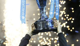 Novak Djokovic of Serbia holds up the ATP World Tour Finals tennis trophy as he poses for photographers after defeating Rafael Nadal of Spain at the O2 Arena in London, Monday, Nov. 11, 2013. (AP Photo/Kirsty Wigglesworth)
