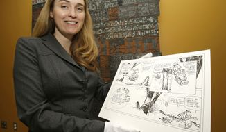 "Juli Slemmons holds a ""Calvin and Hobbes"" comic by cartoonist Bill Watterson at the Billy Ireland Cartoon Library and Museum on the Ohio State University campus in Columbus, Ohio. (AP Photo)"