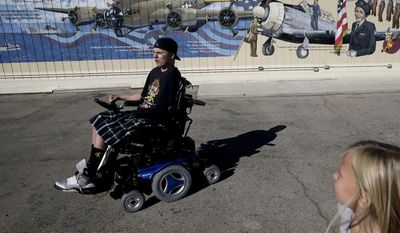 Jerral Hancock, a 27-year-old Iraq war veteran who lost his left arm and was paralyzed from the waist down in a bomb explosion, and his daughter, Anastasia, arrive at Lancaster High School for a meeting with members of Operation All The Way Home on Monday, Oct. 21, 2013, in Lancaster, Calif. (AP Photo/Jae C. Hong)