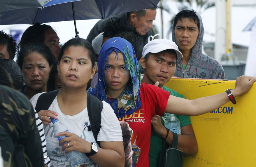 Frustrated families wait in the rain for evacuation flights in Tacloban, central Philippines, Tuesday, Nov. 12, 2013.  Thousands of typhoon survivors swarmed the airport here on Tuesday seeking a flight out, but only a few hundred made it, leaving behind a shattered, rain-lashed city short of food and water and littered with countless bodies.   (AP Photo/Wally Santana)