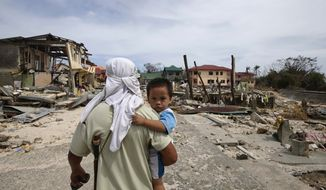 A man walks home with his son Monday Nov. 11, 2013, following Friday's devastating typhoon that lashed Hernani township, in eastern Samar province, in the central Philippines. Typhoon-ravaged Philippine islands faced an unimaginably huge recovery effort that had barely begun Monday, as bodies lay uncollected and uncounted in the streets and survivors pleaded for food, water and medicine. (AP Photo/Bullit Marquez)