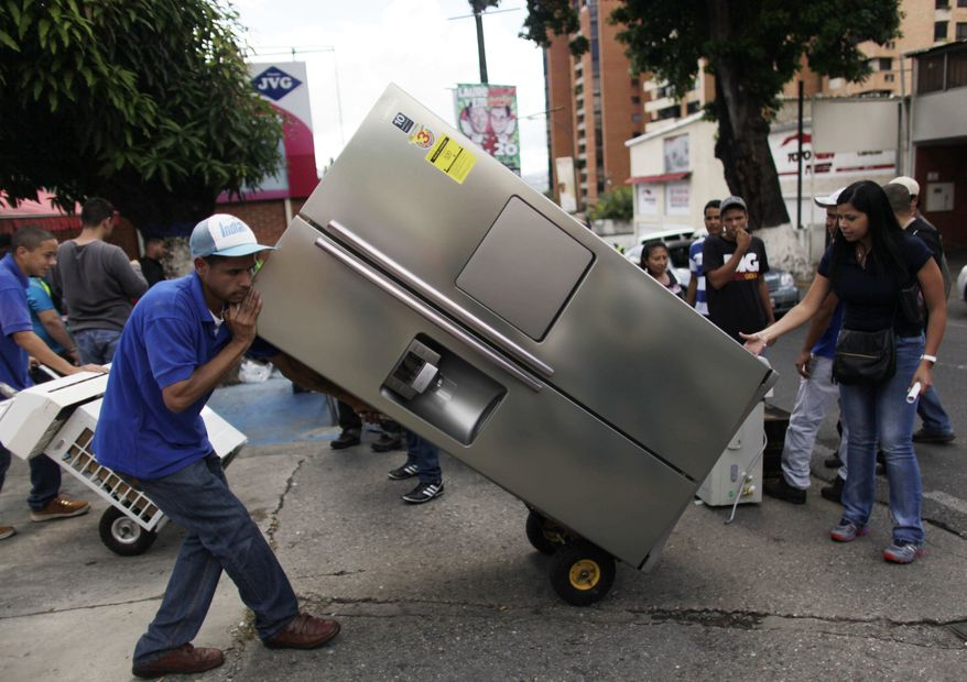 """A man transports a recently purchased refrigerator on a dolly, outside an appliance store in Caracas, Venezuela, Monday, Nov. 11, 2013. President Nicolas Maduro seized control of a nationwide chain of appliance stores Friday seeking to battle inflation and shortages. Shoppers were still arriving Monday to join the hundreds who began amassing over the weekend after price inspectors said they found evidence of """"usury"""" and Maduro ordered the chain Tiendas Daka """"occupation."""" (AP Photo/Ariana Cubillos)"""