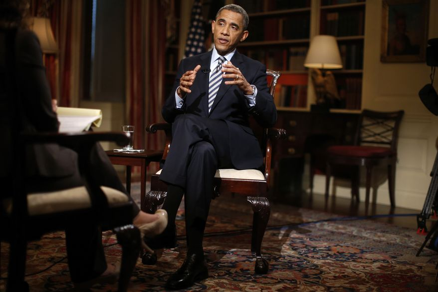 """In this photo taken Friday, Oct. 4, 2013, President Barack Obama speaks during an exclusive interview with The Associated Press in the White House library in Washington. Obama says he'd think about changing the name of the Washington Redskins football team if he were the owner. He said he's sure Redskins fans don't mean offense. But he said Native Americans feel strongly that the name is degrading and that he's not sure that the fans' attachment to the name should override those """"real legitimate concerns."""" (AP Photo/Charles Dharapak)"""