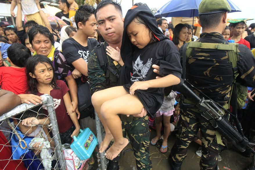 Philippine military personnel try to prioritize children and women first as they wait for evacuation flights in Tacloban, central Philippines, Tuesday, Nov. 12, 2013. Thousands of typhoon survivors swarmed the airport on Tuesday seeking a flight out, but only a few hundred made it, leaving behind a shattered, rain-lashed city short of food and water and littered with countless bodies. (AP Photo/Wally Santana)