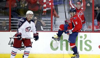 Washington Capitals right wing Alex Ovechkin (8), of Russia, celebrates his game winning goal with Columbus Blue Jackets defenseman James Wisniewski (21) nearby, in the overtime period of an NHL hockey game, Tuesday, Nov. 12, 2013, in Washington. The Capitals won 4-3. (AP Photo/Alex Brandon)