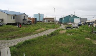 ** FILE ** Wooden boards connect houses in the flood-prone village of Newtok, Alaska, in 2006. The Yup'ik Eskimo community, near Alaska's storm-battered coast, is running out of time as coastal erosion creeps ever closer. (AP Photo/Alaska Department of Commerce)