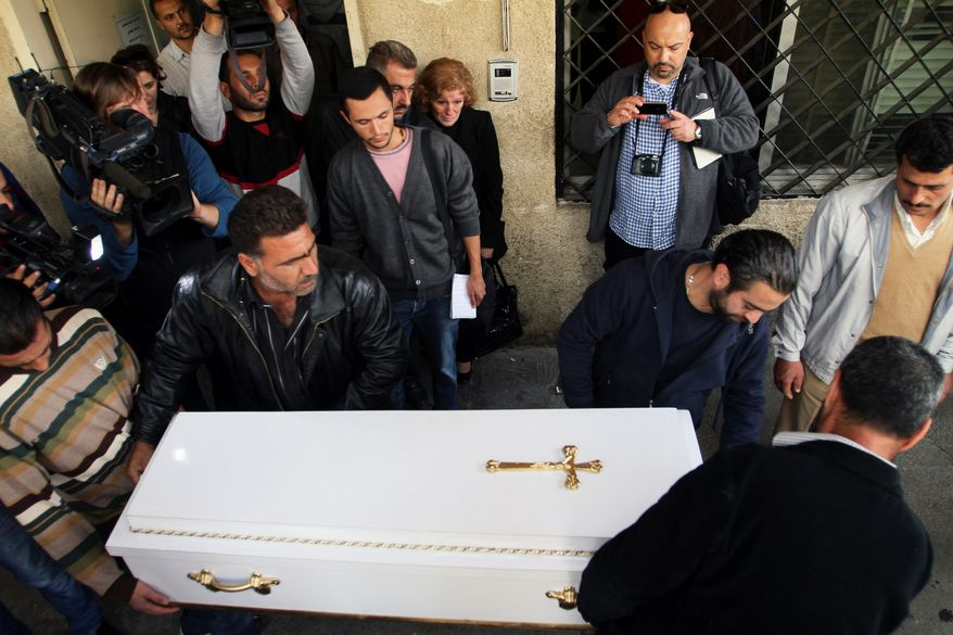On Tuesday, Nov. 12, 2013, bystanders watch pallbearers carry the coffin of one of four Syrian children who were killed the previous Monday in the Bab Sharqi neighborhood of Damascus, Syria. Syria's state news agency said a mortar shell hit a school bus, killing the children and the bus driver. It said four other children and two teachers also were wounded. (AP Photo)