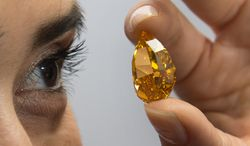 "FILE -In this Nov. 1, 2013 file picture a Christie's employee displays the considered  largest fancy vivid orange diamond in the world, during a press preview in Geneva, Switzerland.  The diamond is estimated to fetch  up to to US $ 20 million, at an auction on Tuesday  Nov. 12, 2013, in Geneva. It's auction time for the filthy rich again in Geneva, where the week's headline-grabbers include the largest fancy vivid orange diamond in the world and another diamond estimated to be worth more than $60 million.Christie's is set to auction off a 14.82-carat rare gem that it says is expected to fetch up to $20 million Tuesday. Sotheby's auctions are headlined by Wednesday's offering of ""The Pink Star,"" a vivid and flawless 59.60-carat diamond estimated to be worth more than US $60 million.   (AP Photo/Keystone,Martial Trezzini,File)"
