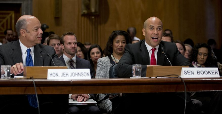 Jeh Johnson (left), President Obama's choice to become secretary of homeland security, listens as Sen. Cory Booker, New Jersey Democrat, speaks on Capitol Hill in Washington on Wednesday, Nov. 13, 2013, during the Senate Homeland Security and Governmental Affairs Committee hearing on Mr. Johnson's nomination. (AP Photo/Carolyn Kaster)