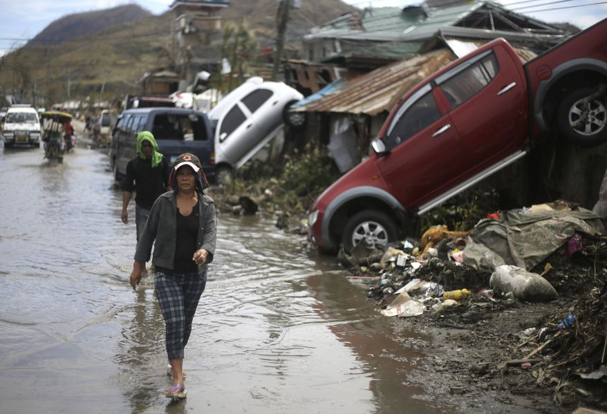 A woman walks past cars swept away by Typhoon Hayan in Tacloban, Philippines, Wednesday, Nov. 13, 2013. Typhoon Haiyan, one of the strongest storms on record, slammed into six central Philippine islands on Friday leaving a wide swath of destruction. (AP Photo/Dita Alangkara)