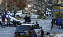 News crews gather where Allegheny County Sheriffs block Crane Ave. above the scene where three students were shot outside Brashear High School in Pittsburgh   Wednesday, Nov. 13, 2013. Police were searching for at least one gunman in some nearby woods and the neighborhood surrounding the school, school and police officials said.   (AP Photo/Gene J. Puskar)