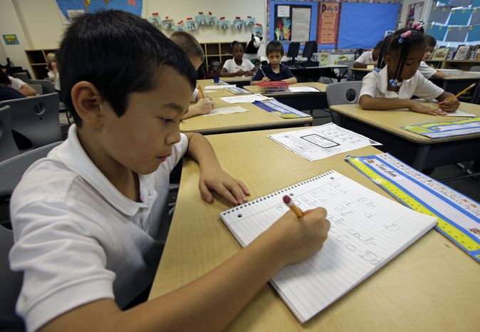 Jaeden Alvarez practices cursive writing at Cleveland K-6 School, Wednesday, Sept. 18, 2013, in Dayton, Ohio. In years gone by, penmanship helped distinguish the literate from the illiterate. But now, in the digital age, people are increasingly communicating by computer and smartphone. No handwritten signature necessary. Cursive writing is not being taught in many schools as some 45 states have adopted Common Core standards, which have eliminated the teaching of cursive writing. (AP Photo/Al Behrman)